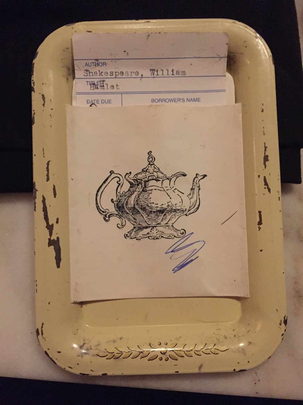 [image description: a vintage cream-colored tray with a notecard printed with a teapot sitting in the tray. Inside the notecard is an old library checkout card for Shakespeare's Hamlet.]