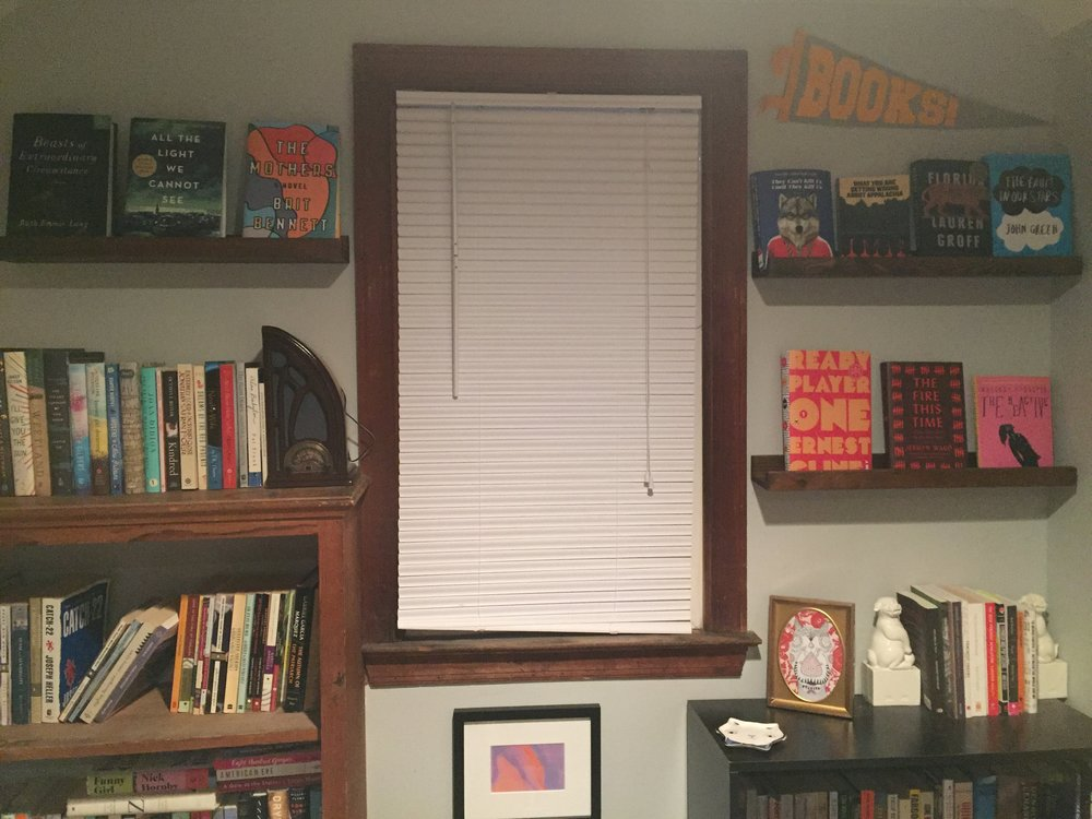 [image description: a small window with a large wooden bookshelf full of books on the left and a small black bookshelf full of books on the right. Above both bookshelves are shallow display shelves where the books on them are facing cover out instead of spine out.]