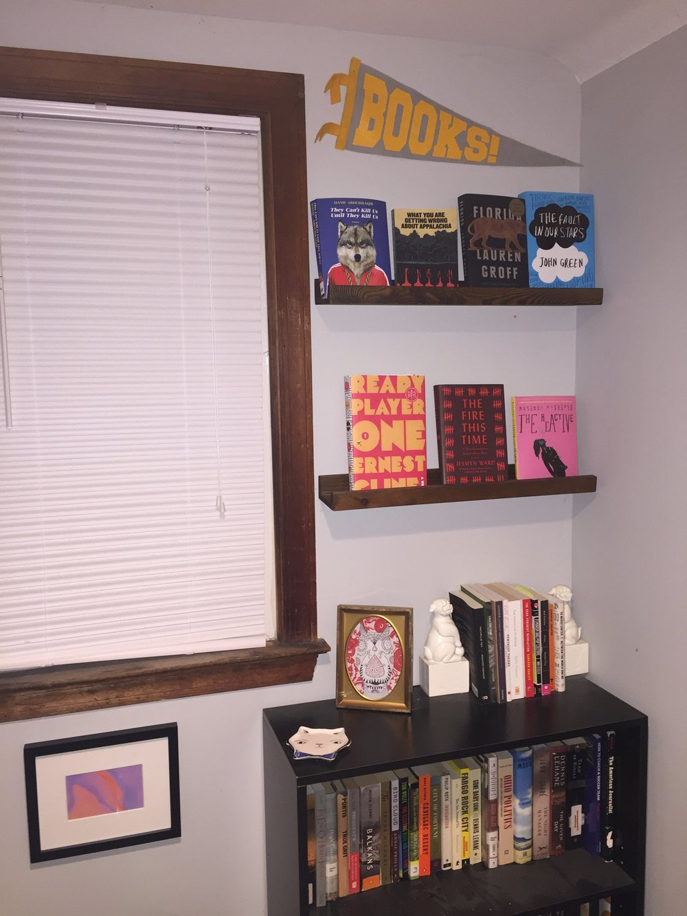"[image description: a wall with a window, a small black bookshelf, and two display shelves with books facing outward. There are also two framed pieces of abstract art and a small triangular flag that says ""books.""]"