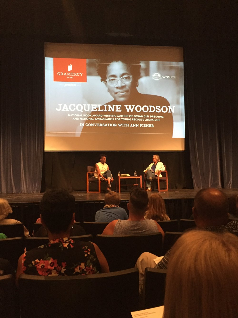[image description: Photo of the stage Jacqueline Woodson spoke on. I was seated several rows back, so the rows in front of me and the people sitting in them are visible at the bottom of the picture. Onstage, Jacqueline Woodson (a black woman) and the person interviewing her (a white woman; more on her in the next paragraph) are sitting with their chairs angled slightly toward each other but where the audience can still see their faces. Above their heads are royal blue curtains and a big dangling screen with Jacqueline's author photo and copy advertising the event.]