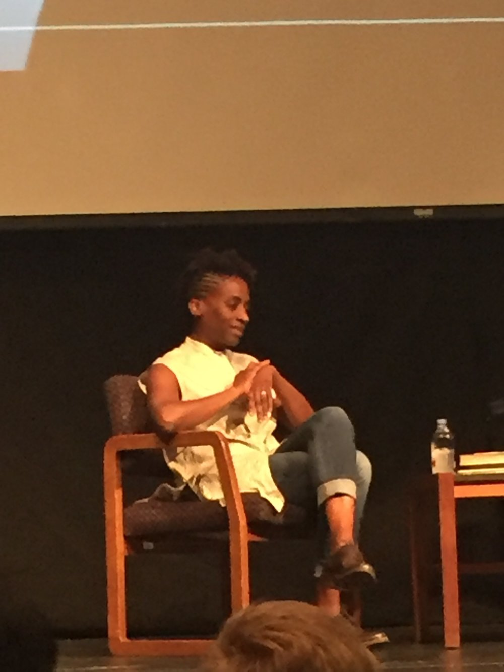 [image description: Jacqueline Woodson on stage at the event. She's a tall, slender black woman in cuff jeans, a cream colored tunic, and brown dress shoes. She's sitting in a wooden chair with her legs crossed and hands together.]