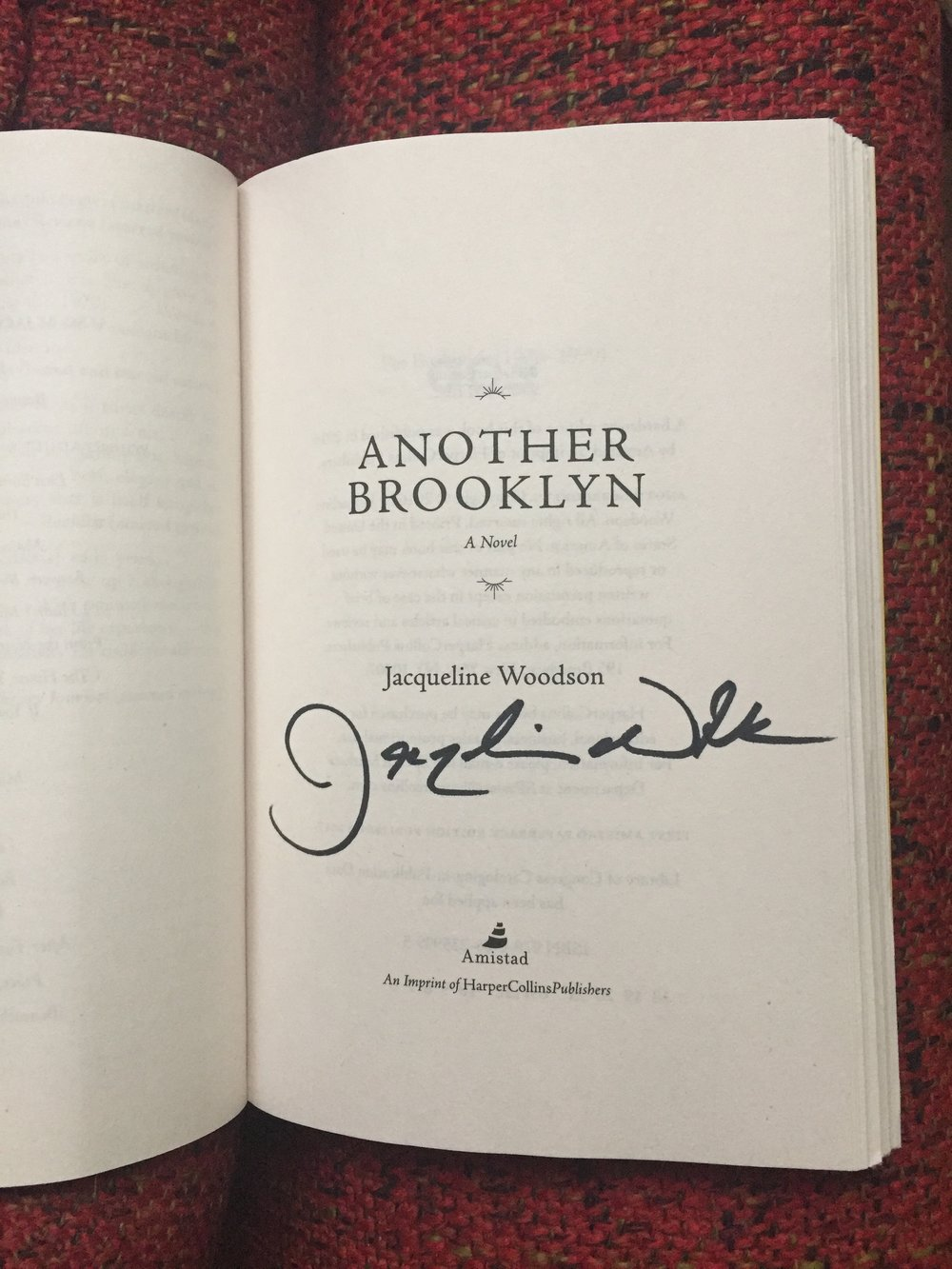 [image description: My signed copy of Another Brooklyn. The photo is an up close of the title page with the author, title, and publisher. This one isn't personalized to me, so the signed part is just Jacqueline's signature.]