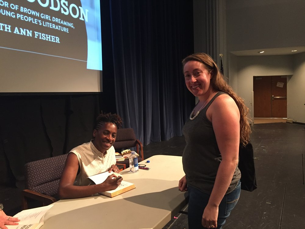[image description: Jacqueline Woodson signing my copy of Brown Girl Dreaming. She's onstage sitting at a long white table and I'm standing across from her while she's signing my book. We're both looking at the camera and smiling.]