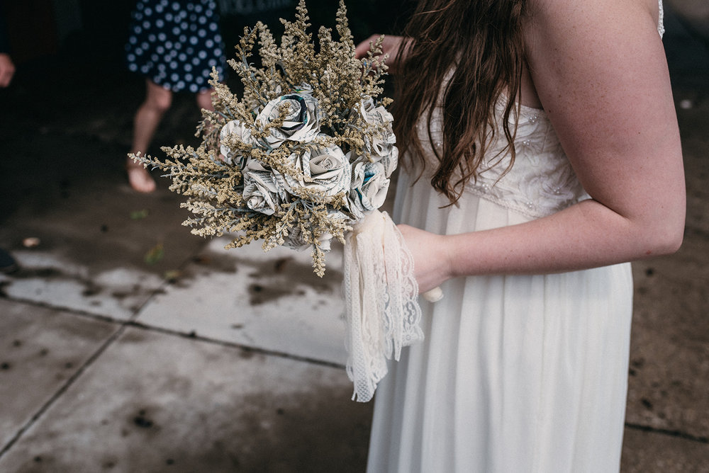 [image description: me (white female, average height and build) in my wedding dress (floor length, not poofy, slightly off-white) holding my bouquet, which is made of flowers constructed from book pages. The bottom part of the bouquet where the stems would be is covered in lace that matches the color of my dress.]