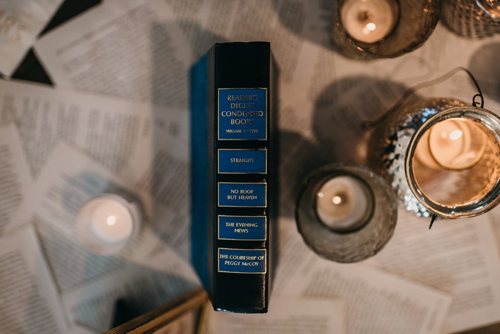 [image description: Close up shot of the spine of a vintage Reader's Digest book beside some silver candle holders with votive candles. The book page table runner is in the background.]