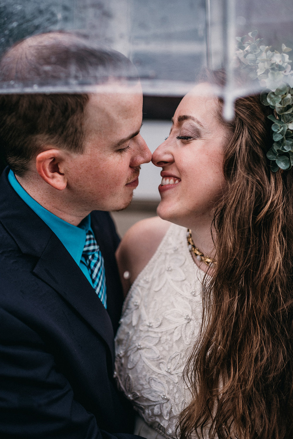 [image description: a photo of my husband and I in our wedding attire. We're facing one another and smiling with our eyes closed and noses touching. There's a clear umbrella above our heads because it was rainy that day.]