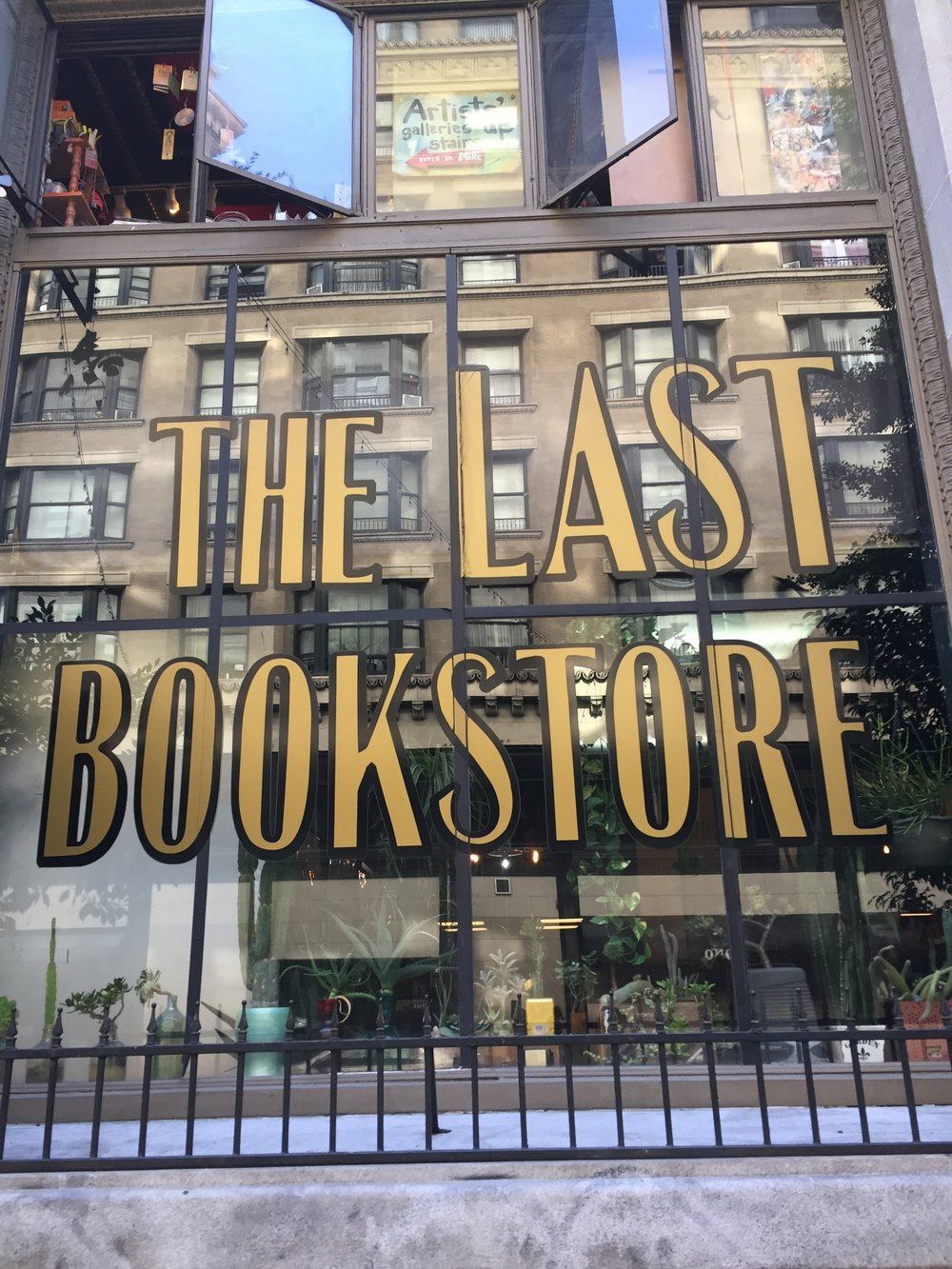 """[image description: the store window of The Last Bookstore. The window has potted plants at the bottom and is reflecting the building across the street and has """"The Last Bookstore"""" painted in gold lettering.]"""