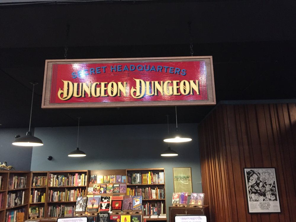 """[image description: The comics and graphic novel section of The Last Bookstores. There's a vintage sign hanging overhead that reads """"Secret Headquarters Dungeon Dungeon.""""]"""