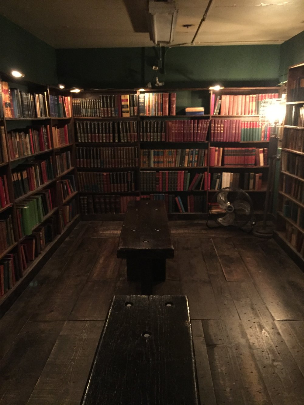 [image description: One of the old bank vaults in The Last Bookstore that's been repurposed into a room with old books. It's dimly lit and there are two benches in the middle for people to sit and read.]
