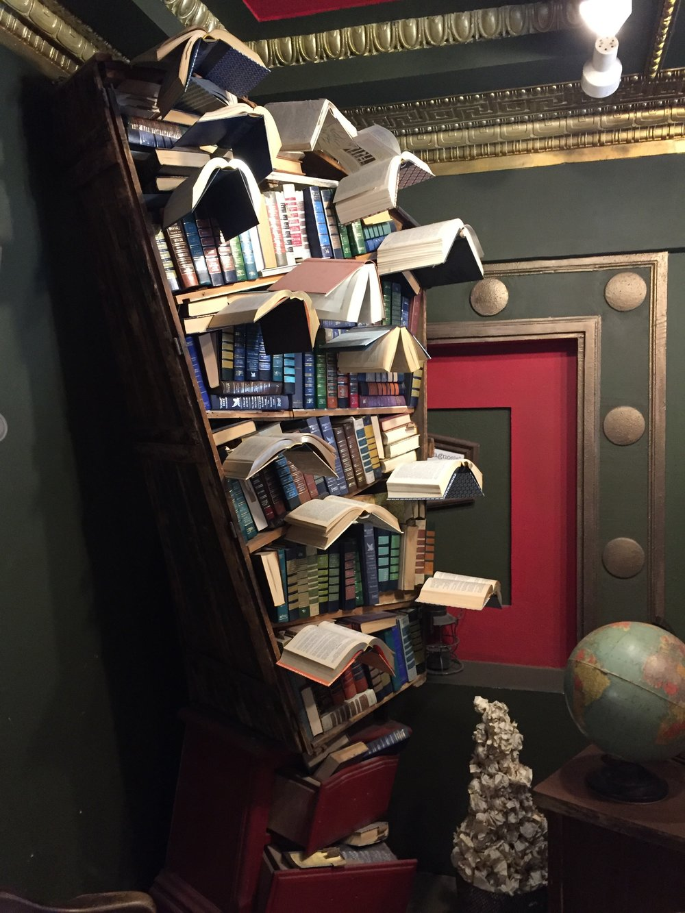 [image description: Another book sculpture where the shelf is oddly shaped––small at the bottom, angular and large at the top. It's packed with old books and other books are placed to look like birds flying off the shelf. There's also a sculpture of a trash can piled high with balls of crumpled paper in a teetering pyramid.]