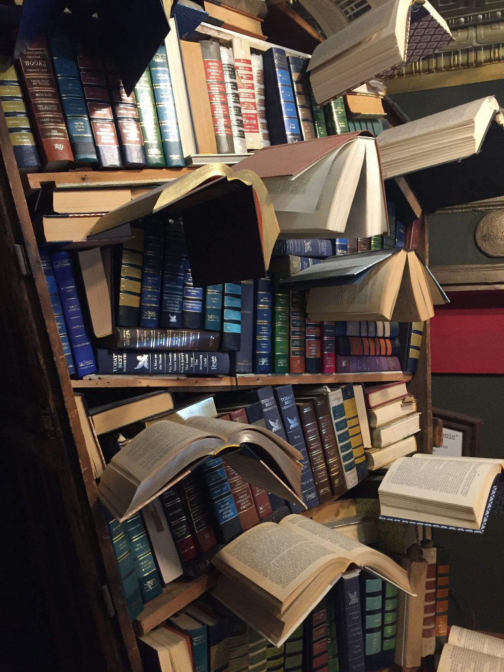 [image description: An up close look at the aforementioned sculpture. The books open like birds are more clearly visible.]