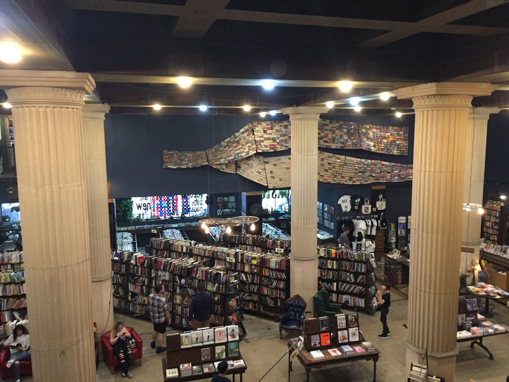 [image description: A bird's eye view of the lower floor of the bookstore from the balcony of the bookstore. There are large fluted columns from floor to ceiling, the massive book sculpture across the back wall, rows and rows of books, and shoppers browsing throughout.]