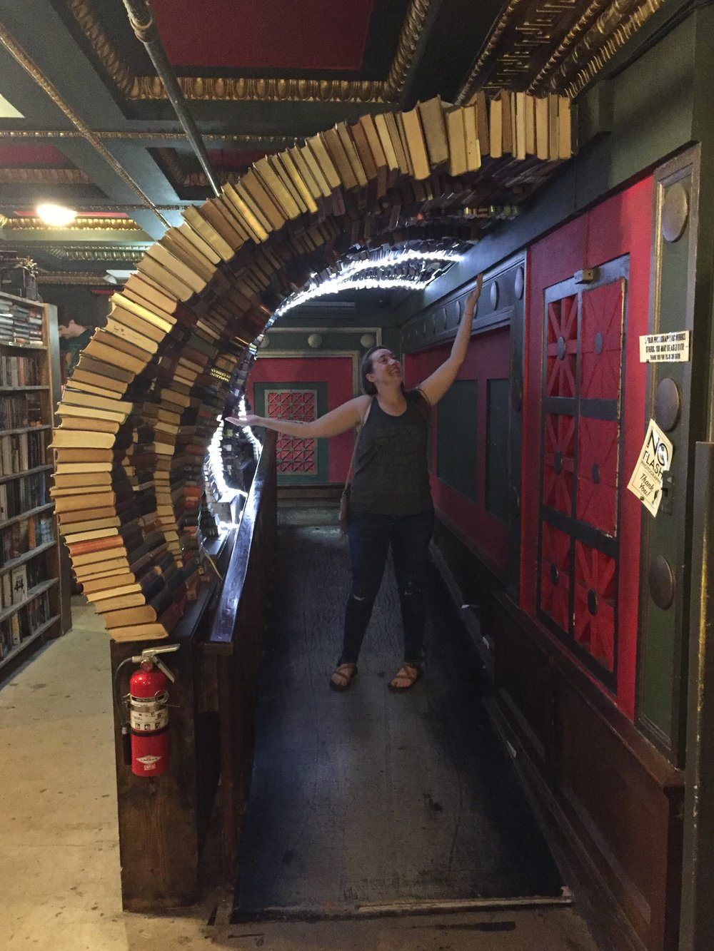 [image description: A low ramp with arcs of books overhead. I'm standing on the ramp with my arms outstretched, smiling up at the books. I'm a white woman of average height and build, with long hair, wearing jeans, sandals, and a gray tank top.]