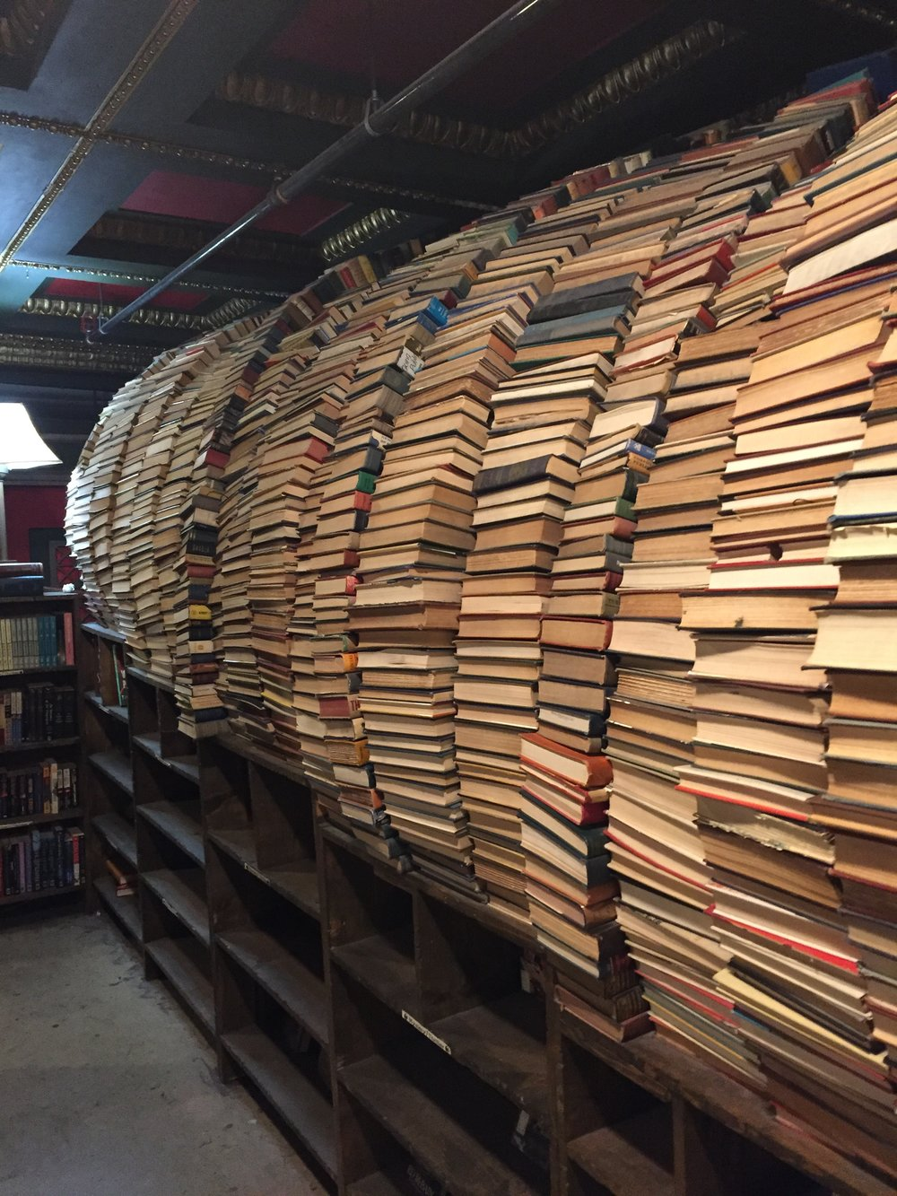 [image description: A view of the back of the aforementioned archway of books over the ramp. It's a wall of stacked books, curving from the top of wide, low shelf at the bottom to the wall where it meets the ceiling on the other side.]