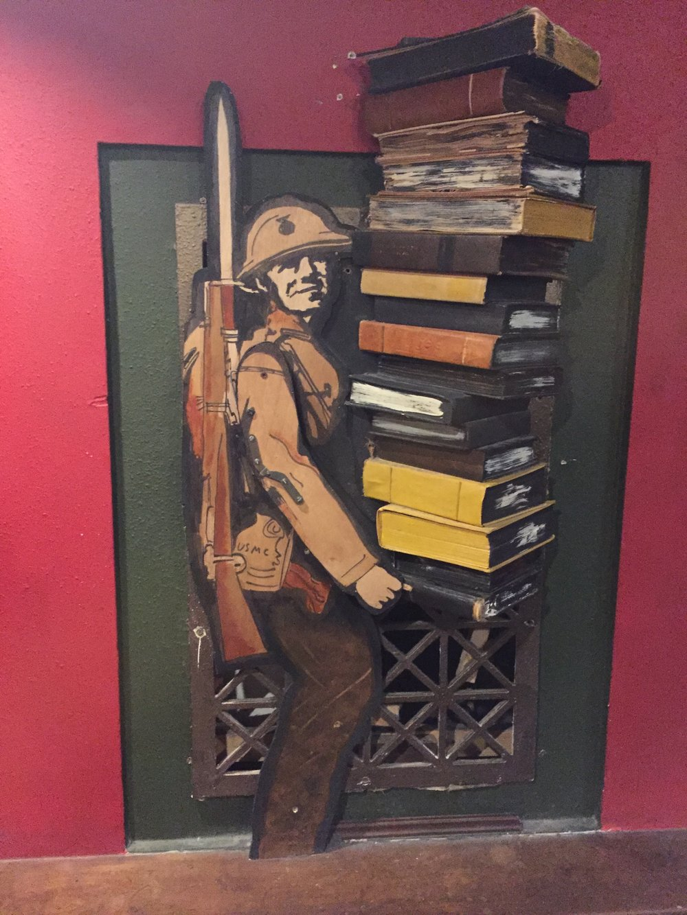 [image description: A piece of book art on the wall in front of an old air grate. It's a soldier, similar in appearance to those in World War I (dressed in all brown with a rifle with a bayonet slung over his shoulder), holding a stack of books that's nearly as tall as he is.]