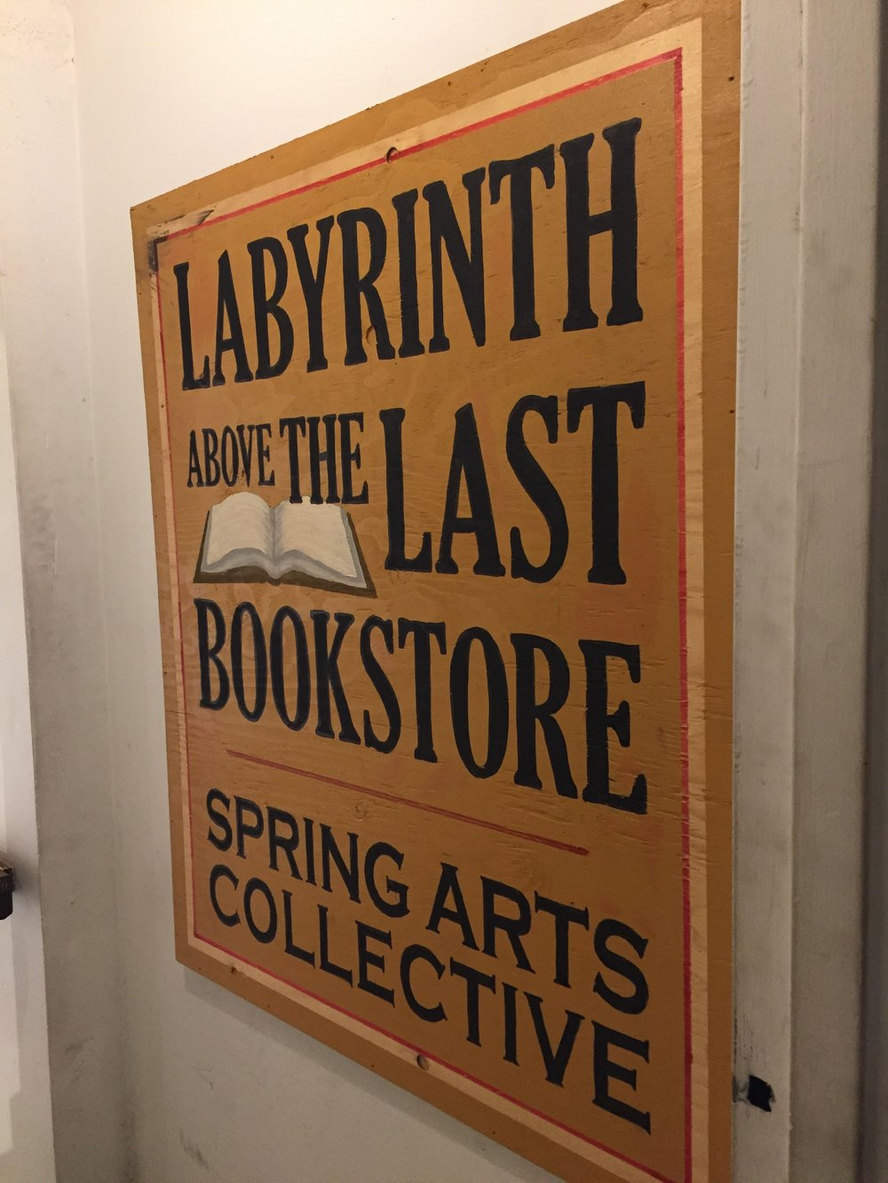 """[image description: A yellow sign on the wall with black text that reads, """"Labyrinth above The Last Bookstore."""" Then below, the words, """"Spring Arts Collective,"""" referring to the artist retail spaces the bookstore rents out to local artists.]"""