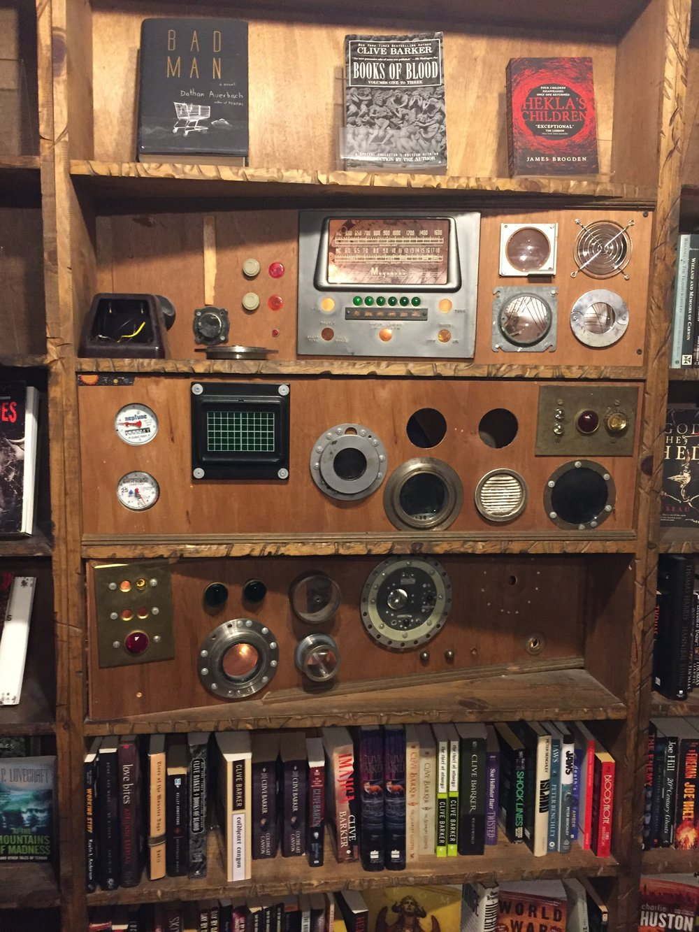 [image description: A sculpture built into a bookshelf. It's a series of portholes, dials, radio knobs, switches, and gages all put together haphazardly.]