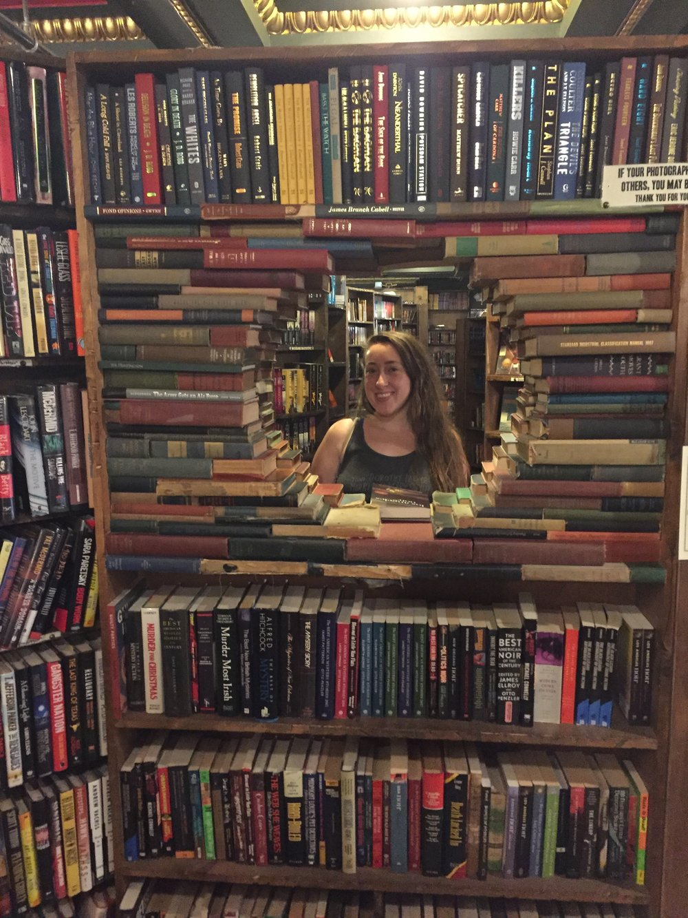 [image description: A sculpture built into a bookshelf. In this one, it's old books laid on their sides and arranged in a way to make a circular window through the bookshelf. The photo is of me as seen through the window of books. I'm smiling at the photographer.]