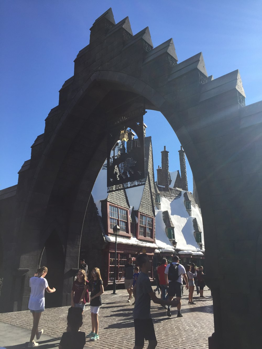 [image description: A large stone archway that serves as the entrance to Harry Potter World, aka a replica of Hogsmeade. There are tall, (fake) snow-covered shops in the background and a bunch of tourists gathering around the entrance.]