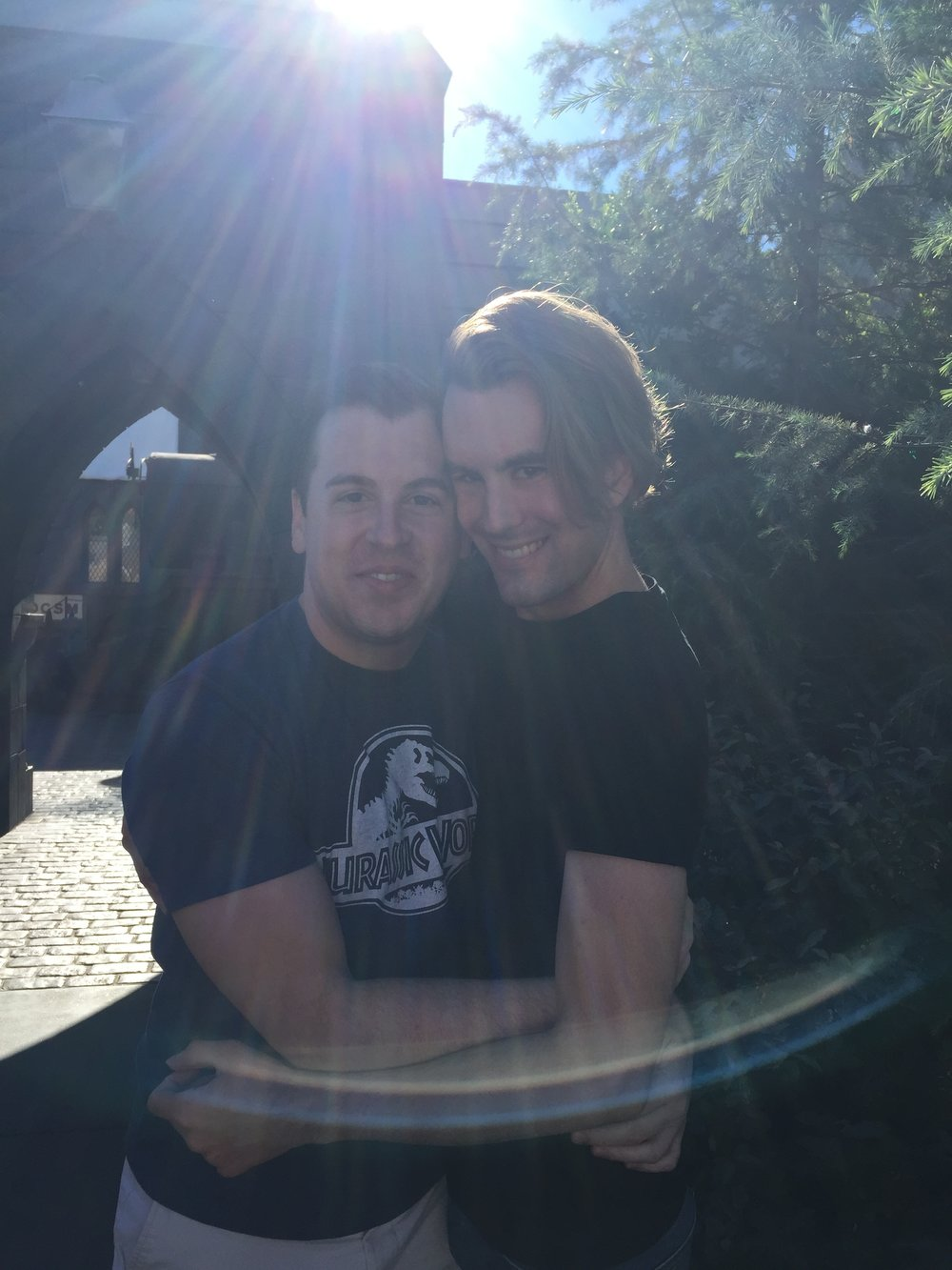 [image description: My best friend, Ethan, and his partner, Kyle, in front of the archway to Hogsmeade. Kyle is a white man wearing white shorts and a blue Jurassic Park shirt and he and Ethan have their arms around each other and are smiling at the camera. The sun is above them and the rays, which are visible in the photo, are shining down on them.]