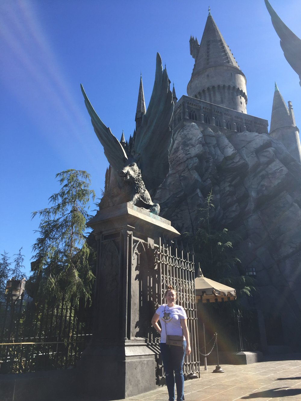 [image description: Me standing in front of the gates of the Hogwarts castle. There are tall black gates with large columns on either side, each with a statue of a boar with massive outstretched wings. The castle looms large in the background. I'm smiling at the camera and have one hand on my hip.]