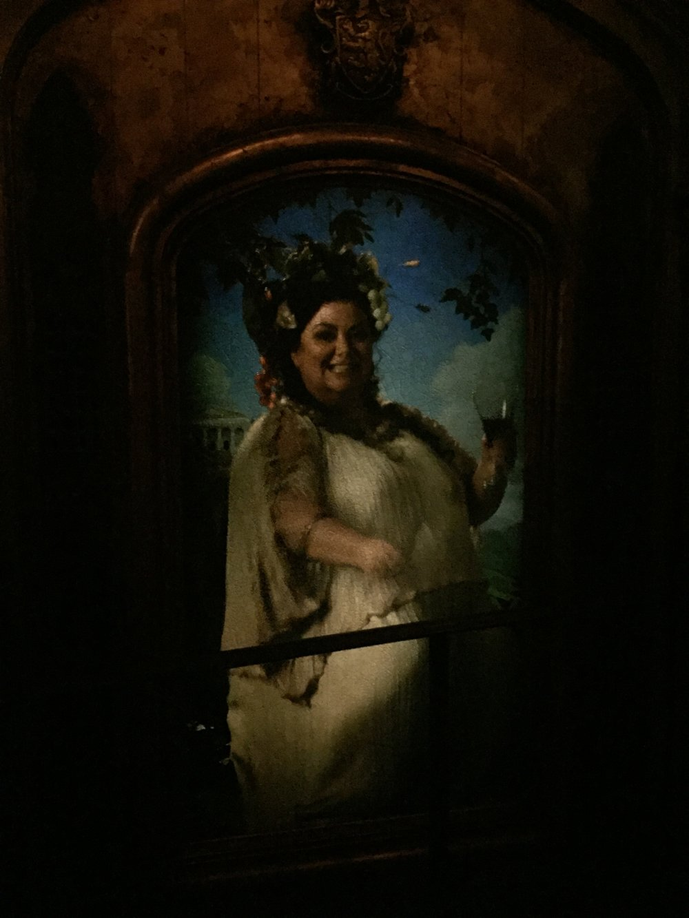 [image description: A portrait of The Fat Lady (JK Rowling's words, not mine) who guards the Gryffindor common room. She asks for passwords for entrance. It's a tall portrait of a woman in a white dress holding a glass of wine and with grapes in her hair. Her dress and the painting are Greek in style.]