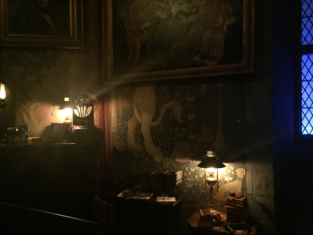 [image description: A corner of the Gryffindor common room. It's dark and difficult to see, but there are old looking paintings on the walls, including one of a unicorn. There's also a mantle above the fireplace with a lamp, radio, and camera resting on top. Beside that, there are two small, low tables with piles of books and letters and another lantern.]