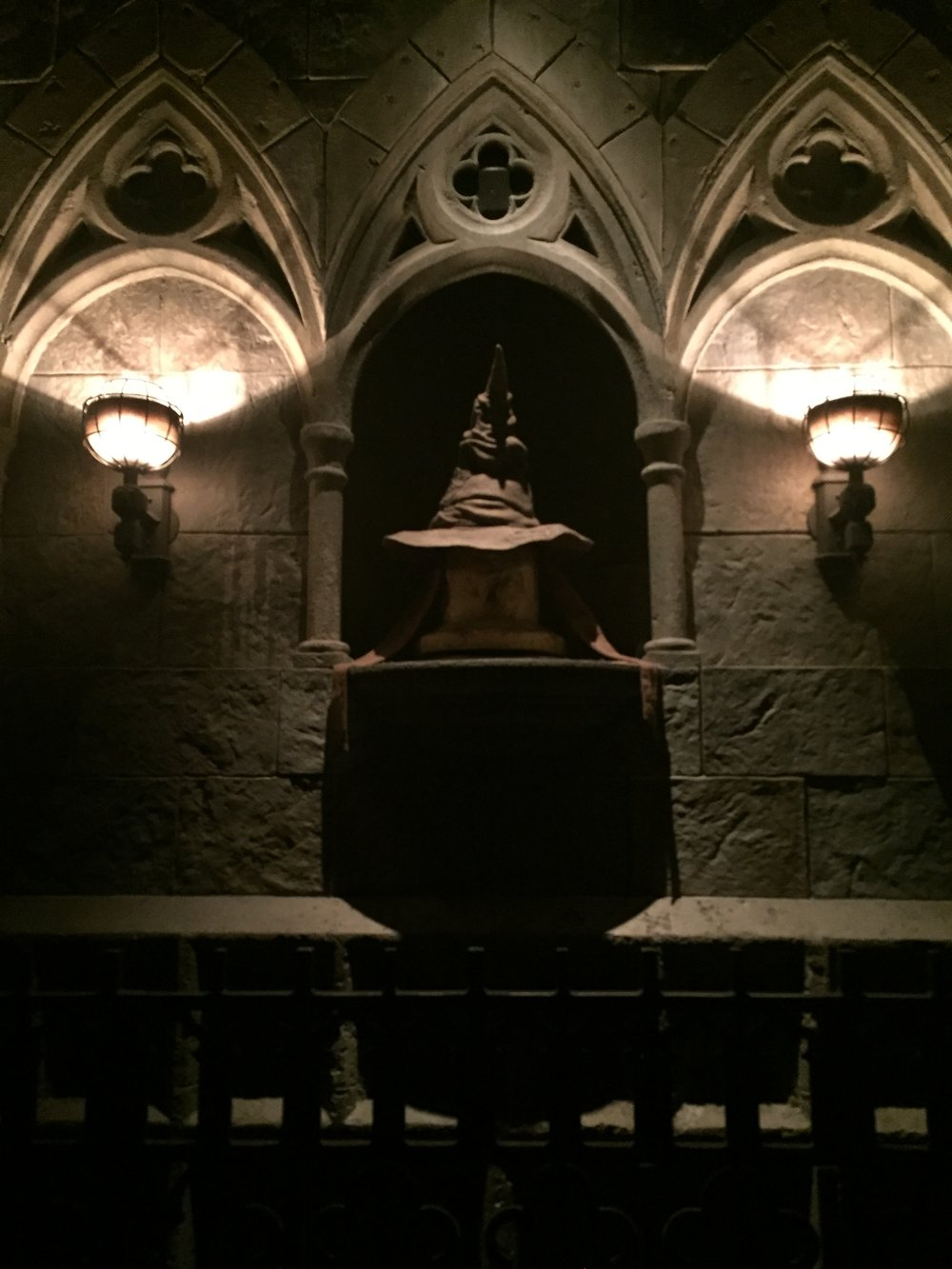 """[image description: Three small alcoves with the sorting hat on a pedestal in the middle with lamps on either side illuminating it. The sorting hat is a brown, pointy """"witch"""" hat with a scowling face made by the hat's wrinkles.]"""