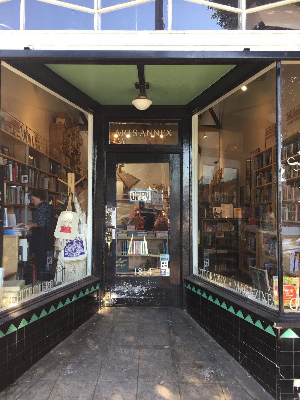 [image description: The shop window of the arts annex of Skylight Books. It's a narrow entrance with tall windows full of books. The entranceway has black tile with green triangles on the wall leading in.]