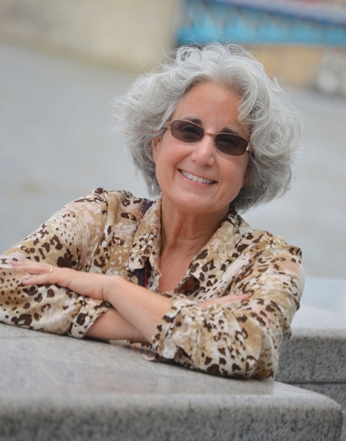 [image description: A photo of author TK Thorne. She's a white woman with gray curly hair and is wearing sunglasses and a leopard print button up blouse. Her arms are crossed and she's leaning on a stone pillar.]