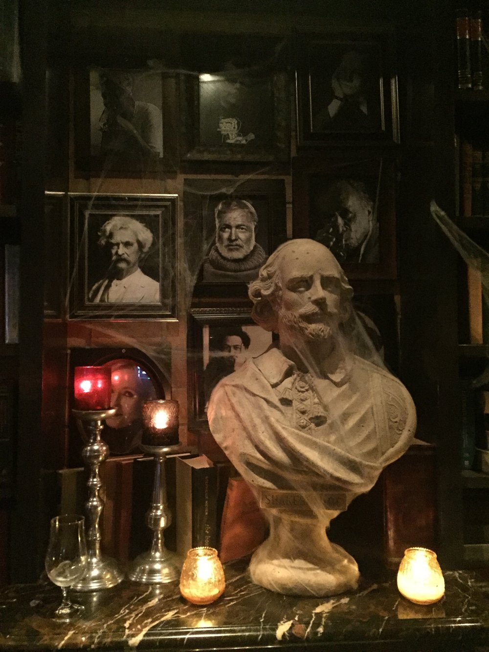 [image description: a marble mantle with a bust of Shakespeare, candles, and silver candlesticks sitting on it. In the background there are framed photos of various writers, including Hemingway and Twain.]