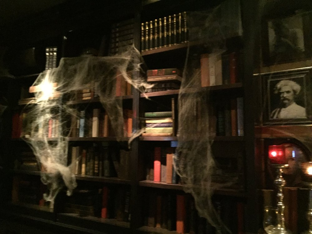 [image description: a zoomed out shot of the previous scene. The bookshelves with fake cobwebs are more visible.]