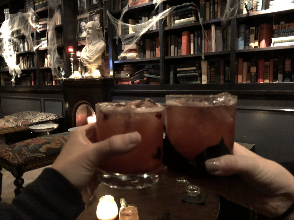 [image description: a close up of two hands––mine on the left and a friend on the right––toasting each other with our cocktails.]