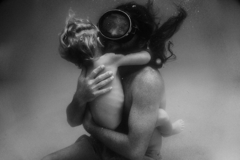 Father and son embracing underwater taken by Twyla Jones