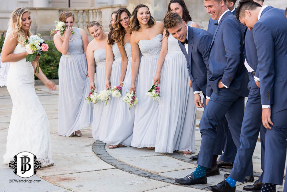 A bride and her bridesmaids looking at the groomsmen as they are all lifting their pant legs to reveal their socks, taken by the couple's Maine wedding photographer.