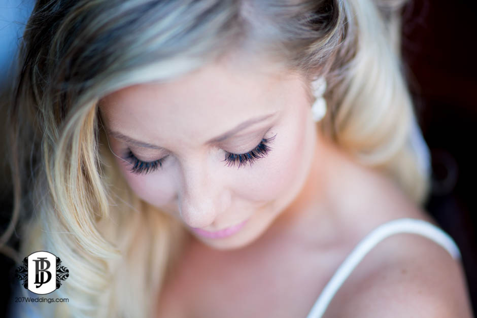 A Maine wedding photographer's close up portrait of a bride looking down to show her hair and makeup