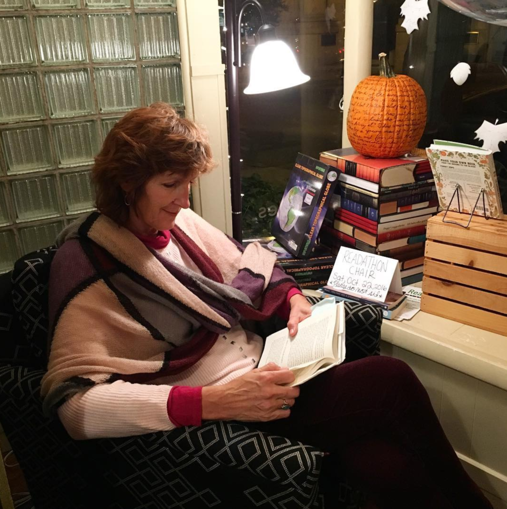 A reader enjoys a book and a comfy chair for a good cause at the October 22, 2016 Curious Readathon event at Curious Iguana bookstore, Frederick, MD.