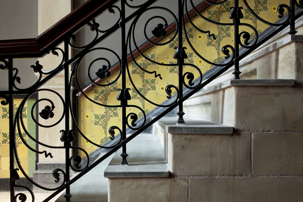 Tiled stone and wrought iron staircase at The Conservatorium Hotel Amsterdam | Design Hunter