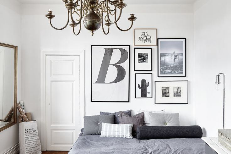Black and white picture wall with grey cushions