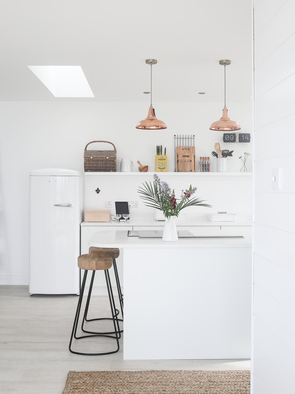 White Scandi style minimalist kitchen with copper lighting | Design Hunter