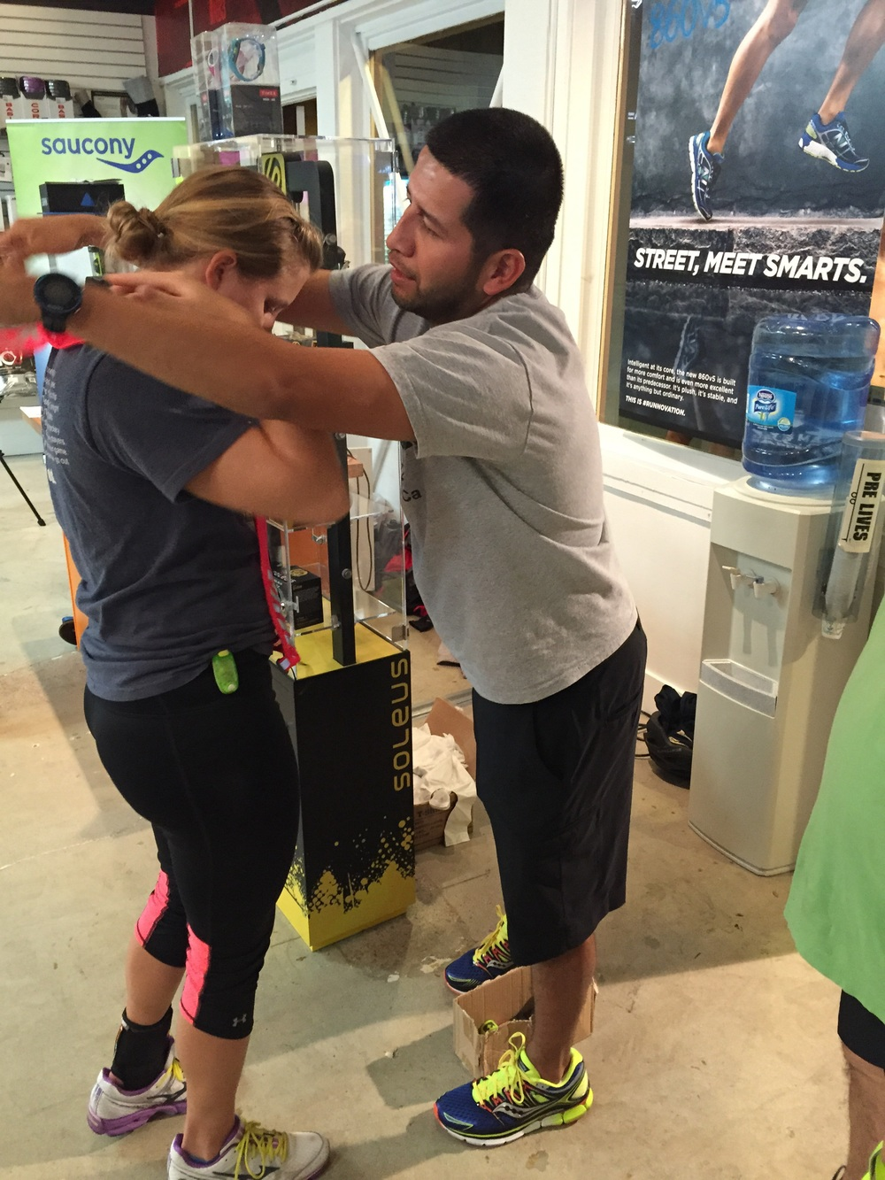 OSCAR AT MOVIN SHOES HELPING A RUNNER WITH HER HEADLIGHT