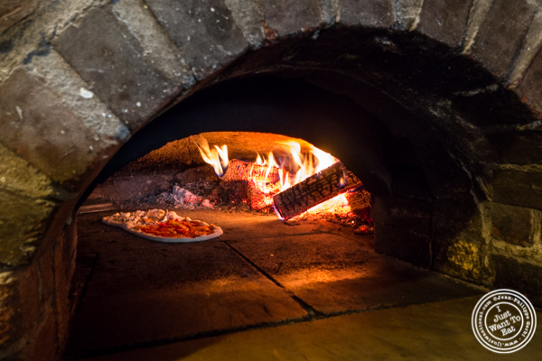 Cooking the pizza in a wood fire oven at Numero 28 Pizzeria, NYC, New York
