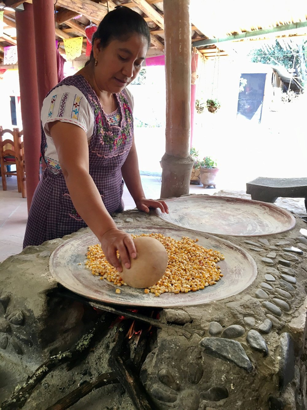 Reyna roasts corn on a hot clay comal.