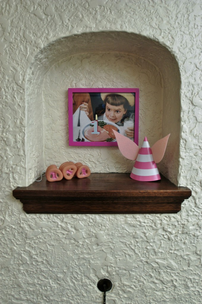 Above the fireplace – pig snouts, a pig-ear party hat, and a framed vintage ham advertisement.