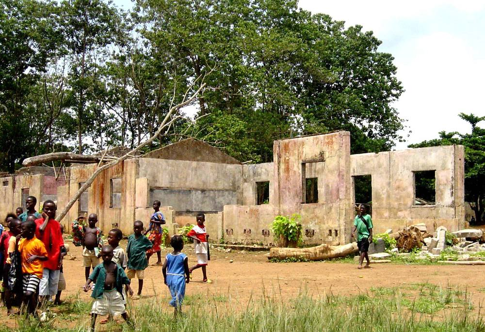 """School destroyed by Sierra Leone Civil War"" by Laura Lartigue. Licensed under Public domain via Wikimedia Commons."