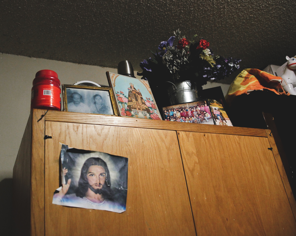 The Acharya home is filled with signifiers of identity. As a refugee family, they hold on to as much as they can, from old family photographs, to new religions. Their apartment is adorned with Hindu alters and posters, as well as statues and photos of Jesus, the new American god they have skeptically accepted into their home.