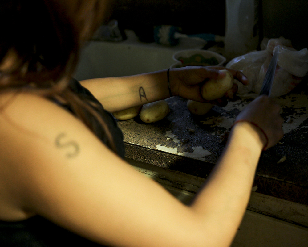 Whoever comes home first in the evenings is responsible for starting dinner for the family, so Sita starts slicing potatoes as soon as she gets home from school. On her arms are two tattoos of her initials Sita has cut into herself. Tattoo and skin markings are heavily correlated with religion and identity in Hindu culture.