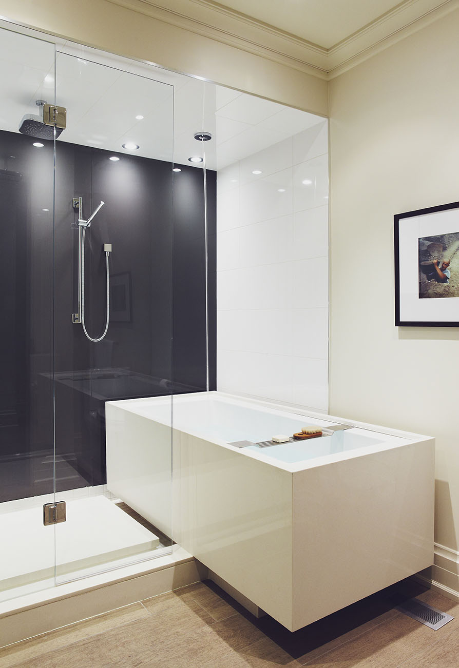 When designing the master bathroom, we wanted to create a space with both a tub and shower, but there was limited room to work with. The idea came forward to have a cantilevered tub, positioned sideways, and projecting from the glass-enclosed shower. Providing the most direct solution, water fills the tub from the ceiling. Heated porcelain flooring perfectly mimics the reclaimed European oak wood flooring throughout the main floor of this Victorian home.