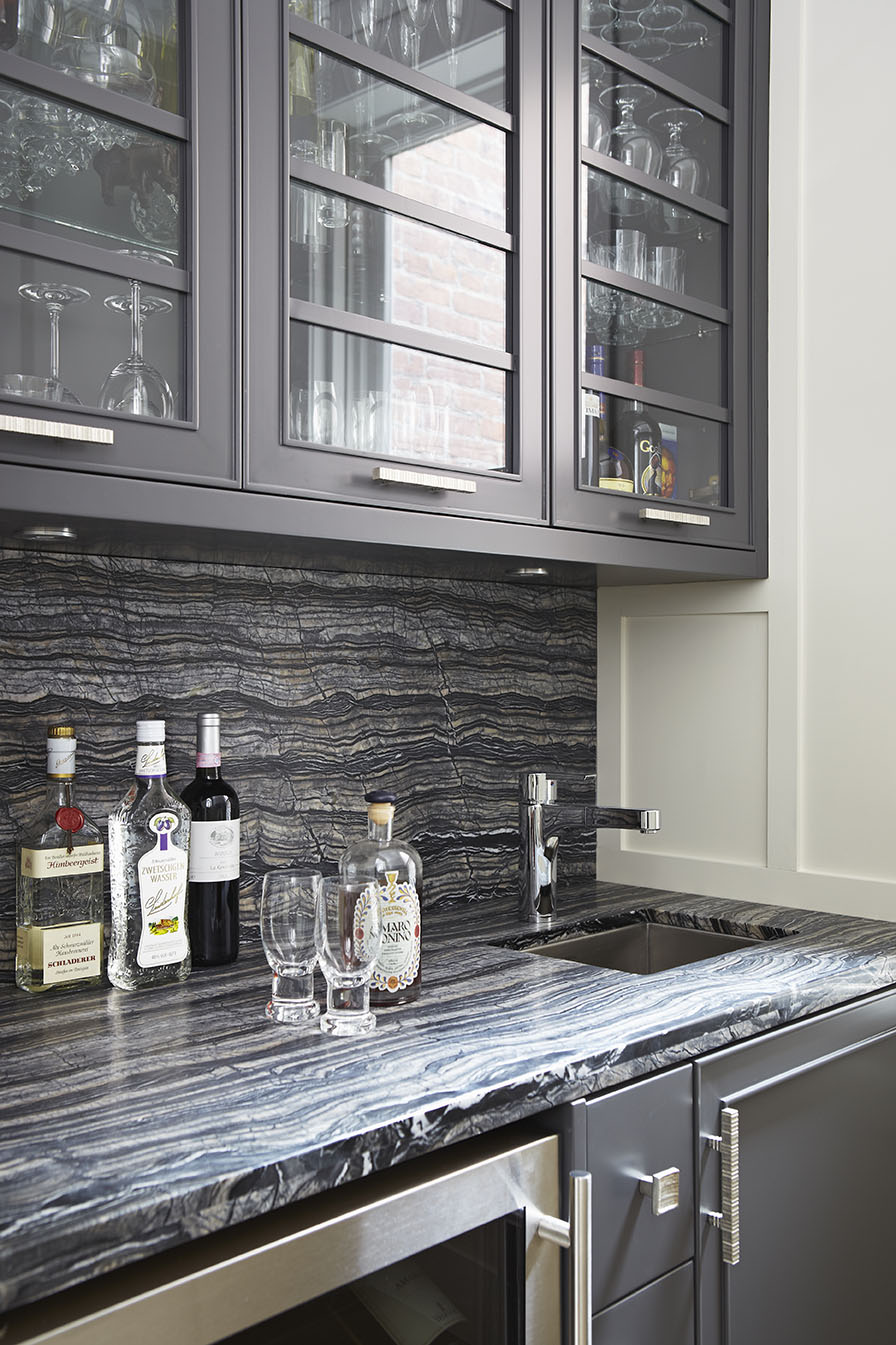 This butler's pantry may be small in size, but does not compromise on functionality and luxury. Glass cabinet doors give a feeling of openness and are reminiscent of the kitchen design. Silverwave marble used for the countertops proves to be a particularly beautiful and serviceable material. The marble was leathered through a brushing process, raising the grain to make a dramatic striated statement.