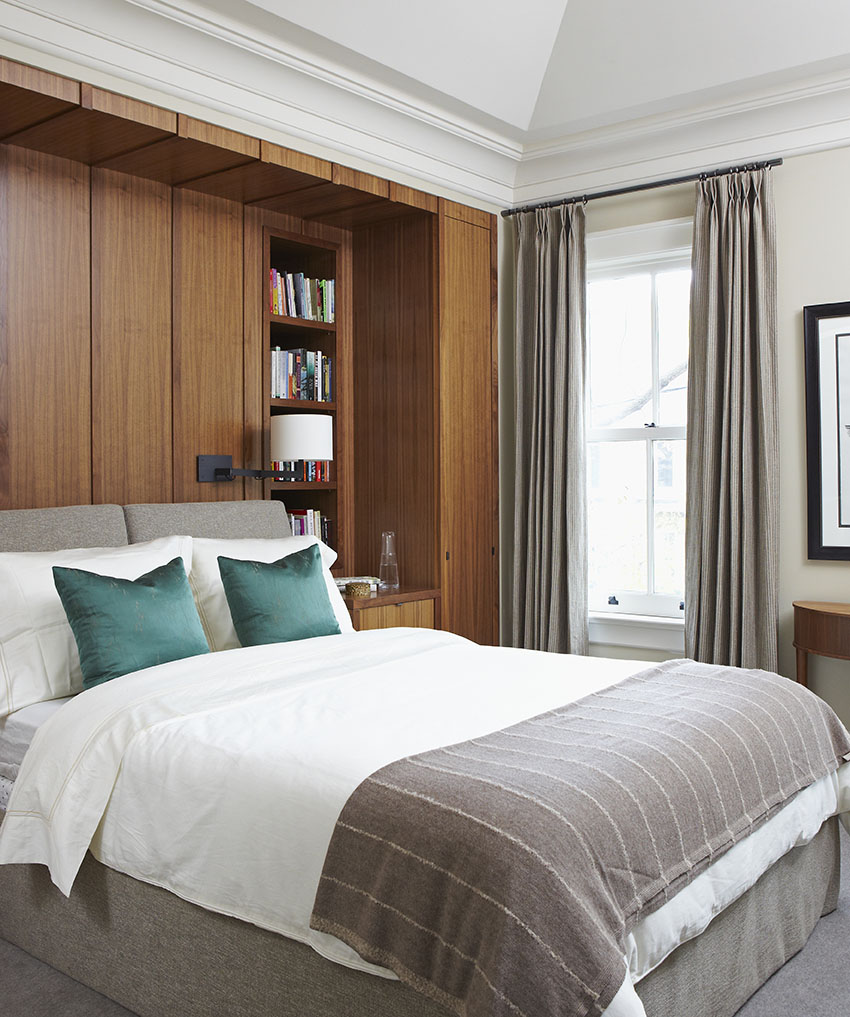 In this Neo-Victorian home, the architecture was integrated with a contemporary interior, creating a natural transition. Board and batten style walnut panelling surrounds the bed and conceals a chimney flue as well as a pull-out shoe closet. Vaulted ceilings add an element of architectural interest and grandeur to the room.